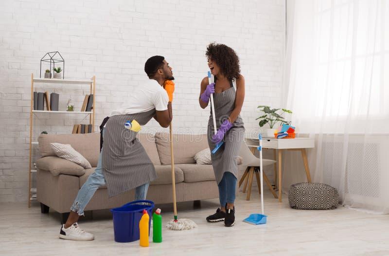 Jong paar schoonmakend huis, die pret met zwabber en bezem hebben royalty-vrije stock foto