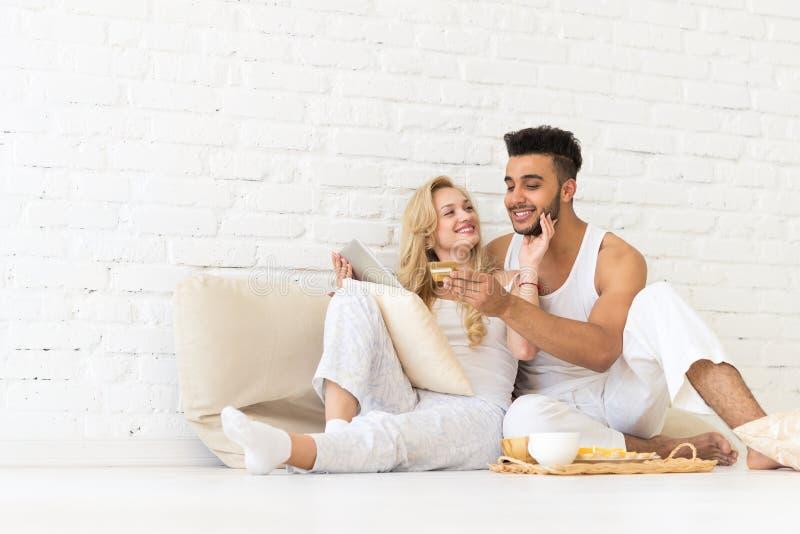Jong Paar Sit Floor die, Spaanse Man Vrouw van de de Creditcard Online Betaling van de Tabletcomputer de Minnaarsslaapkamer gebru royalty-vrije stock foto