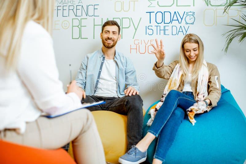 Jong paar tijdens het psychologische adviseren met psycholoog stock foto