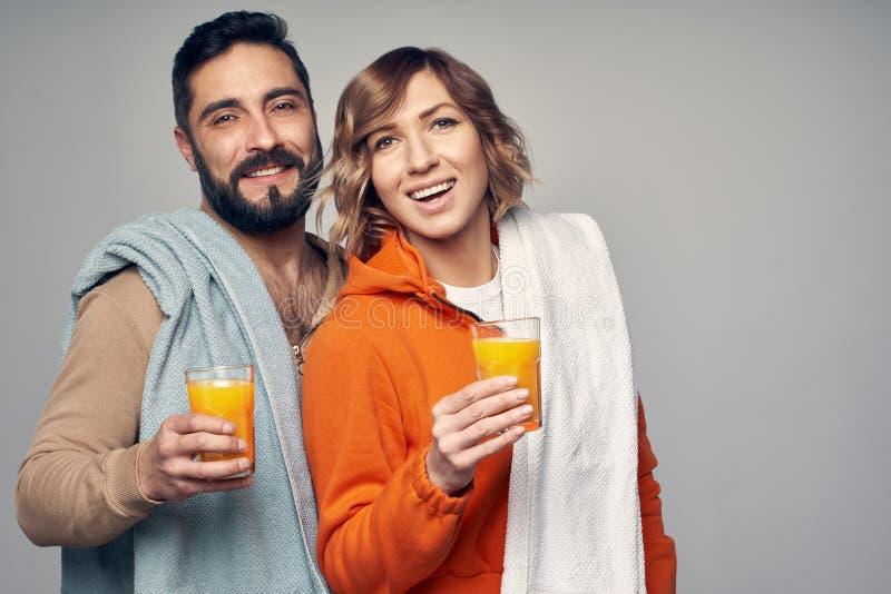 Jong paar in toevallige holdingsglazen jus d'orange stock afbeeldingen