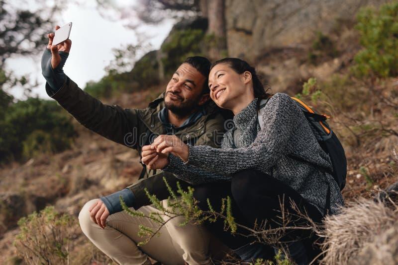 Jong paar uit op stijging in bergen die selfie nemen stock foto's