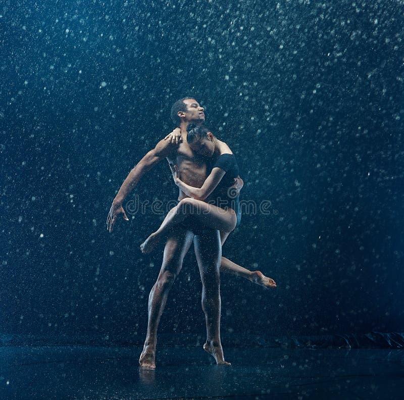 Jong paar van balletdansers het dansen unde rwater dalingen royalty-vrije stock fotografie