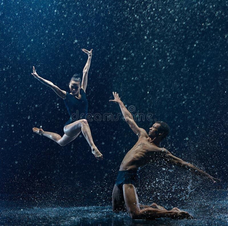 Jong paar van balletdansers het dansen unde rwater dalingen stock afbeelding