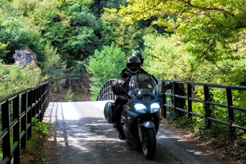 Jong paar van motorrijders die op bosweg in Zagorocho berijden stock foto