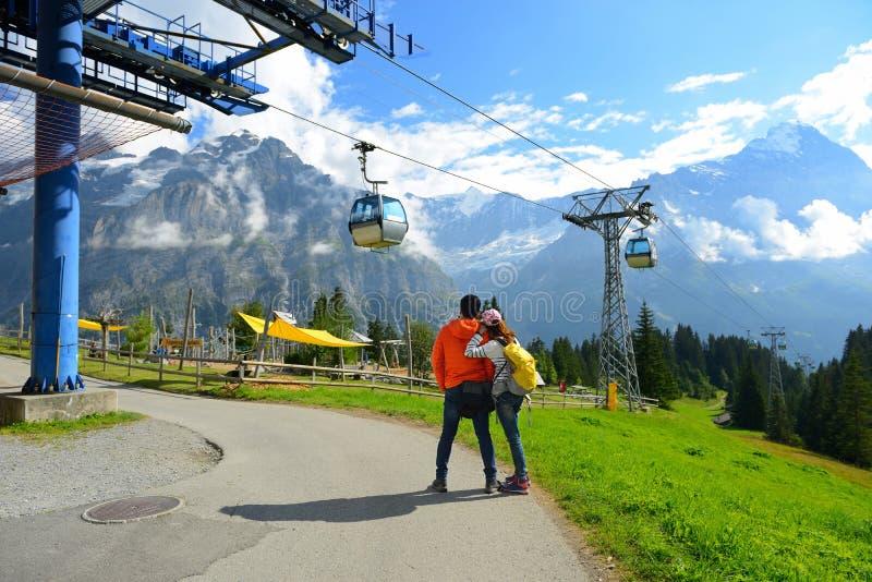 Jong paar van reizigers die van een bergenmening in summe genieten stock foto's