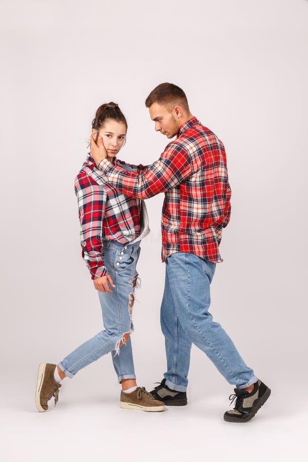 Jong paar van tieners in jeans en in het geruite overhemden stellen isolatie royalty-vrije stock afbeeldingen