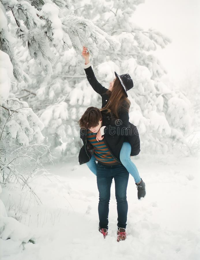 Jong paar in winterwear het genieten van sneeuwval Het verhaal van de liefde stock afbeeldingen