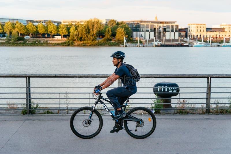 Jong personenvervoer een fiets door rivieroever in Bordeaux royalty-vrije stock foto's