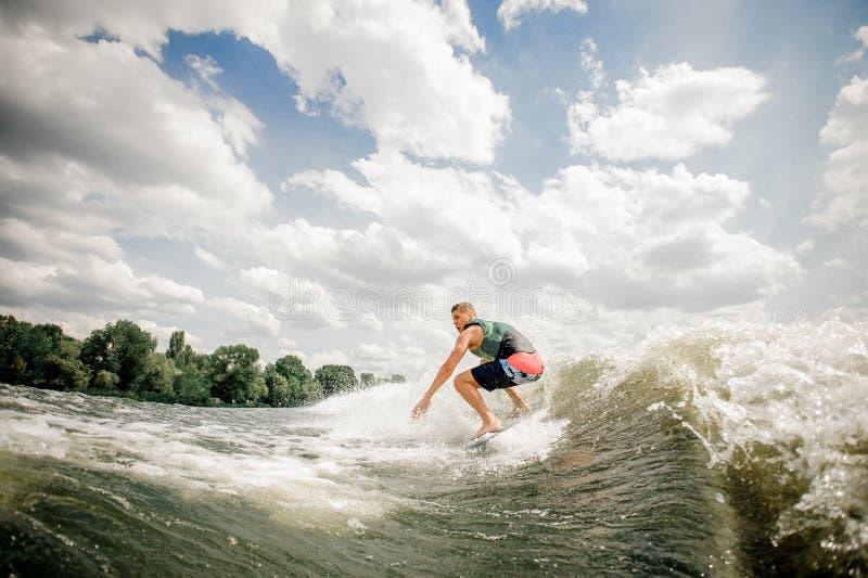 Jong personenvervoer op wakeboard op het meer royalty-vrije stock afbeeldingen