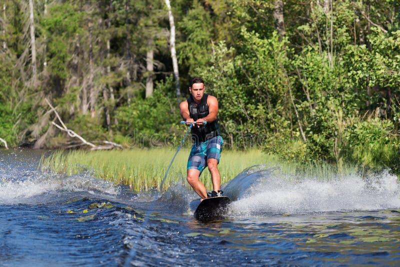 Jong personenvervoer wakeboard op de zomermeer stock foto