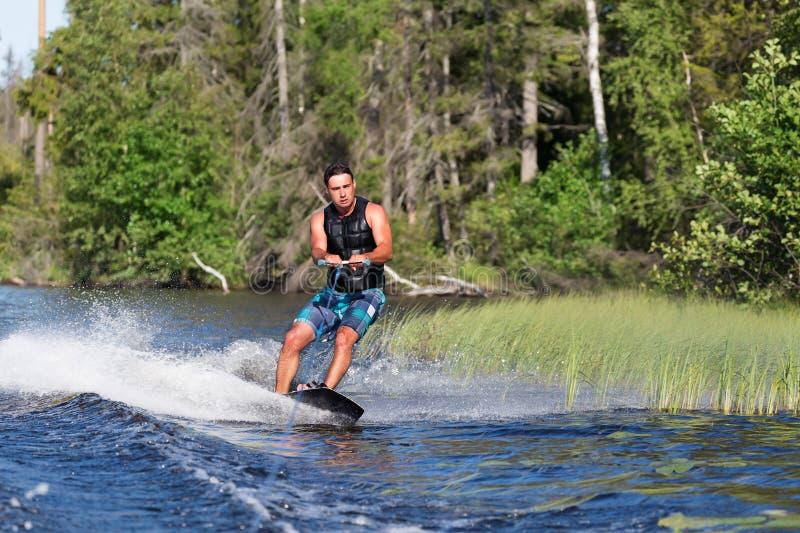 Jong personenvervoer wakeboard op de zomermeer royalty-vrije stock foto's