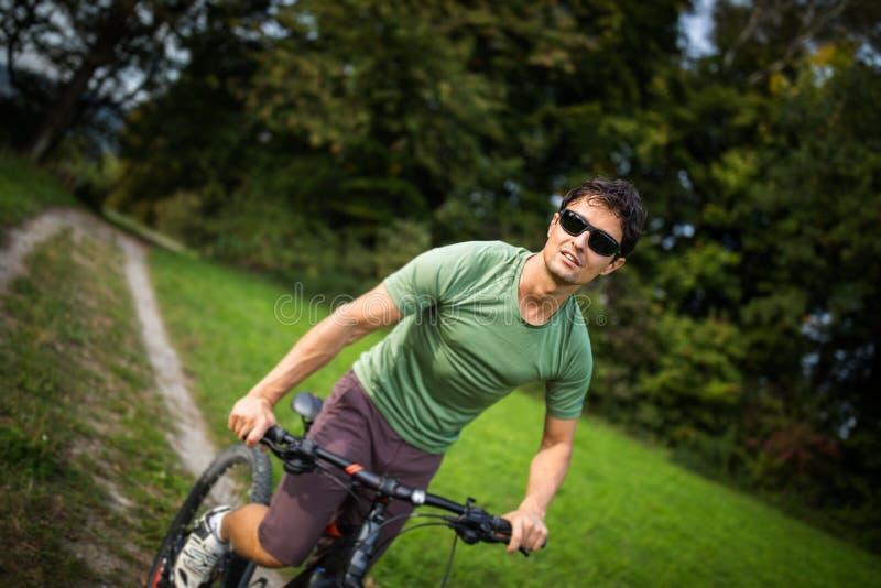 Jong personenvervoer zijn bergfiets in openlucht stock afbeelding