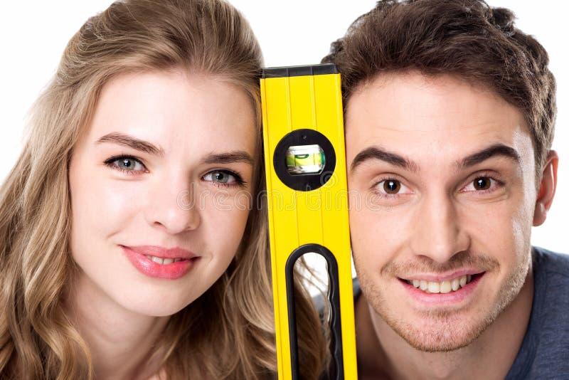 Jong professioneel paar die met niveauhulpmiddel bij camera glimlachen royalty-vrije stock afbeelding