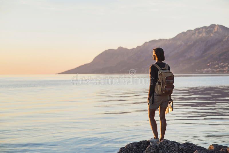 Jong reizigersmeisje die zich met kaart dichtbij het overzees bij zonsondergang, reis, wandeling en actief levensstijlconcept bev stock foto