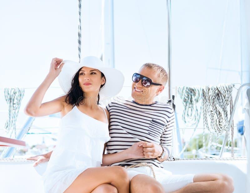 Jong, rijk en aantrekkelijk paar op een varende boot royalty-vrije stock fotografie
