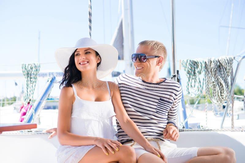 Jong, rijk en aantrekkelijk paar op een varende boot stock foto's