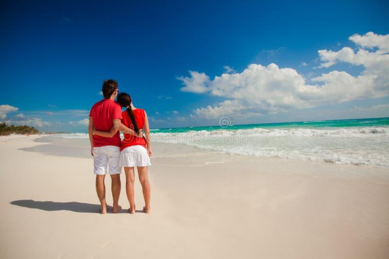 Jong romantisch paar die op exotisch strand binnen lopen stock foto