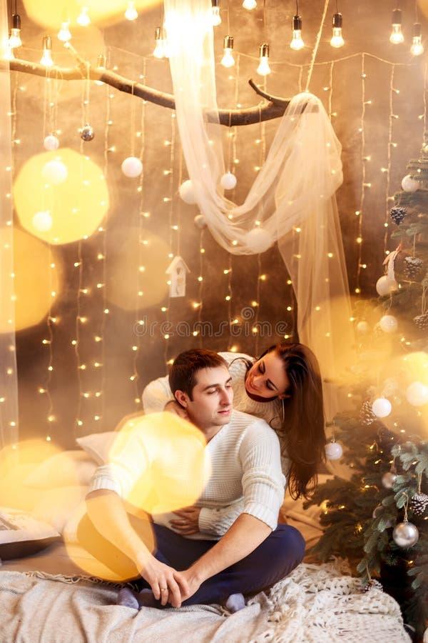 Jong romantisch paar die op nieuwe jaar en Kerstmisvakantie, mooie bokeh wachten stock afbeeldingen