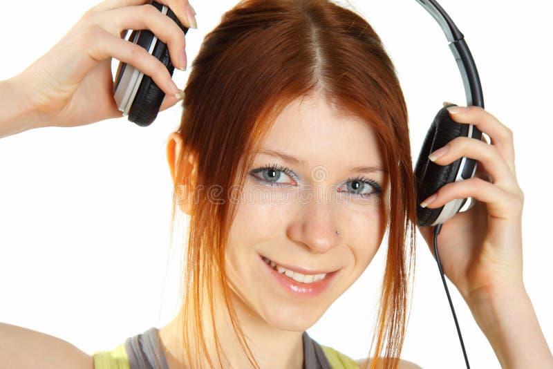 Jong roodharig meisje met hoofdtelefoons royalty-vrije stock afbeeldingen