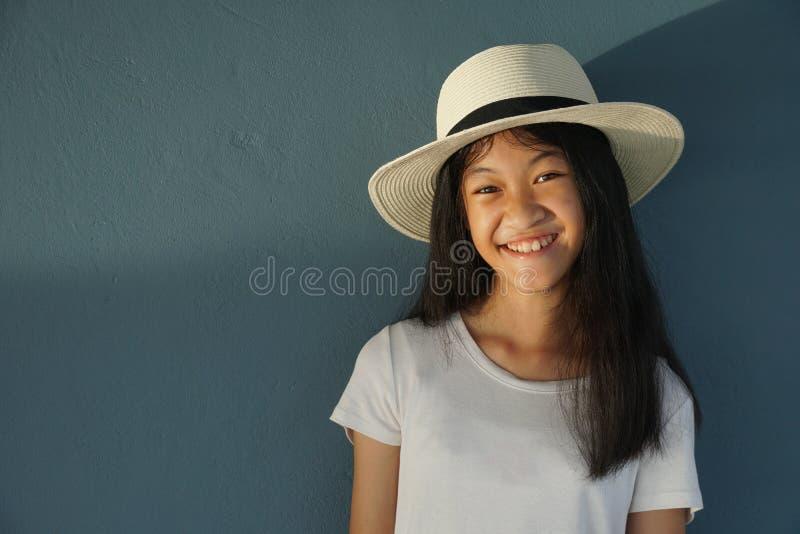 Jong 11s-jong geitjemeisje die lang haar met witte hoed met de zomer natuurlijk zonlicht glimlachen met blauwe muurachtergrond royalty-vrije stock afbeelding