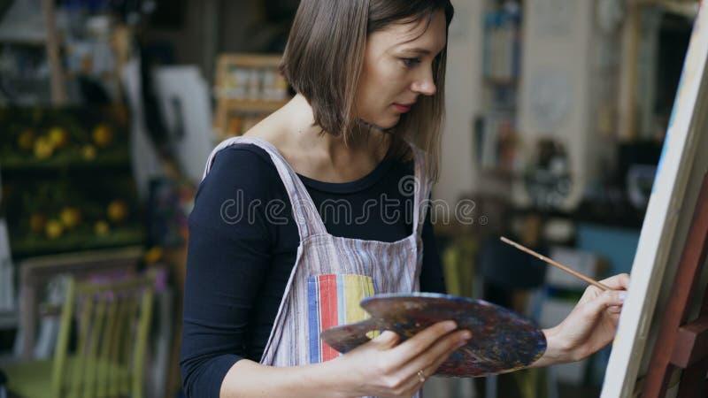 Jong schildersmeisje in schort het schilderen stillevenbeeld op canvas in kunst-klasse stock afbeelding