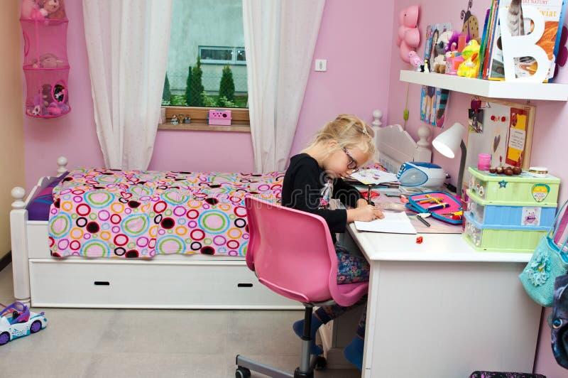 Jong schoolmeisje die thuiswerk doen stock foto