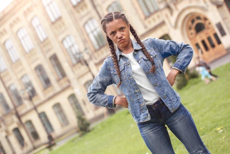 Jong schoolmeisje in jeans die zich bij de handen van de schoolyard op heupen bevinden die opzij boos kijken stock foto's