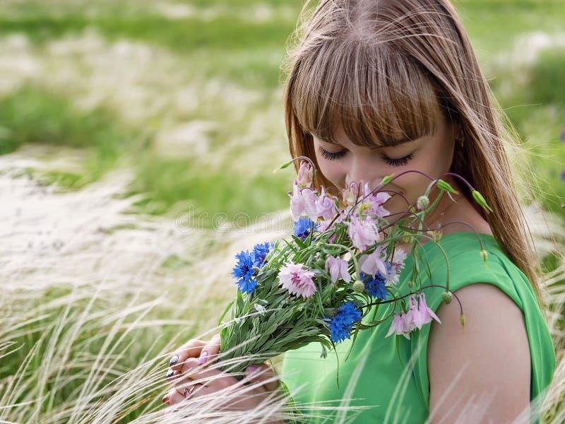 Jong sensueel meisje die een boeket van wildflowers ruiken stock afbeeldingen