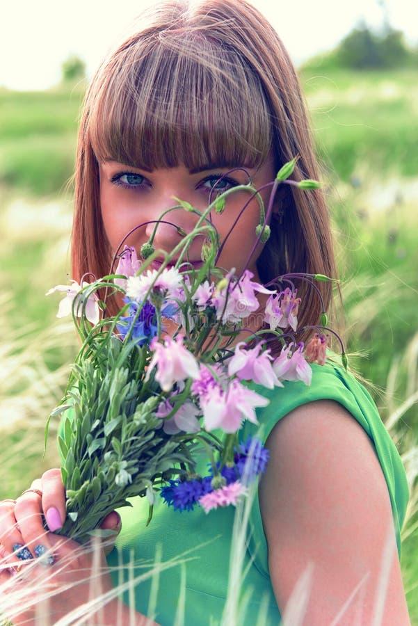 Jong sensueel meisje die een boeket van wildflowers ruiken stock foto