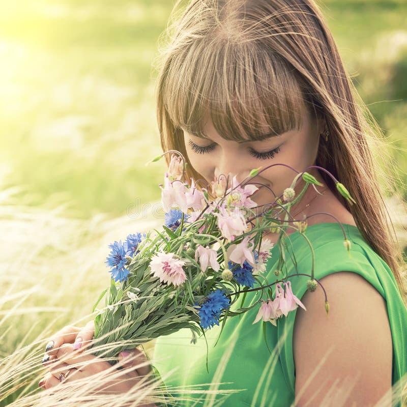 Jong sensueel meisje die een boeket van wildflowers ruiken royalty-vrije stock fotografie