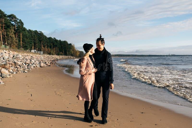 Jong sensueel paar die pret hebben die en op strand lopen koesteren Koud de herfstweer, kustlijn royalty-vrije stock afbeelding