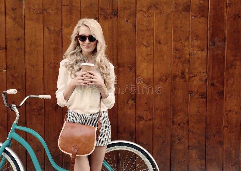 Jong sexy blondemeisje met lang haar met bruine uitstekende zak in zonnebril die zich dichtbij uitstekende groene fiets bevinden  stock fotografie