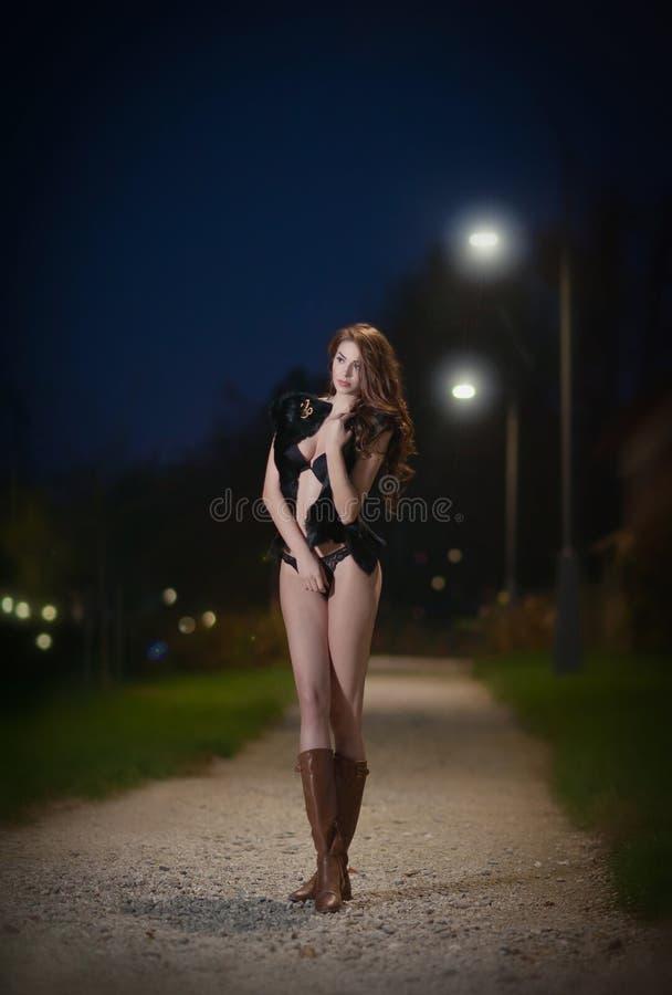Jong sexy meisje op straat bij nacht. Mooi brunette met lange benen openlucht. Sensuele vrouw die leerlaarzen in nacht dragen. Sex royalty-vrije stock fotografie