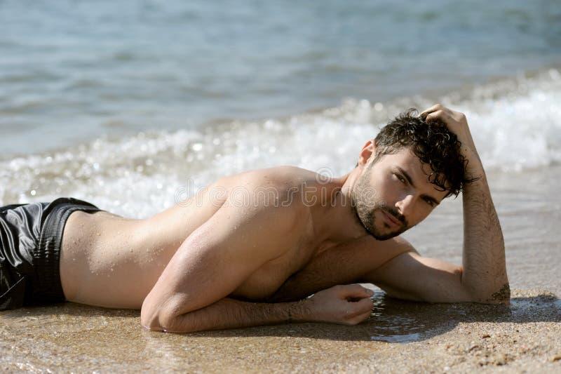 Jong sexy mensenportret die in topless zeewater leggen, royalty-vrije stock fotografie