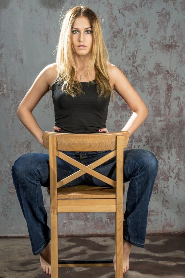 Jong slank blondemeisje in jeans en overhemd die coquettishly stellen stock foto's