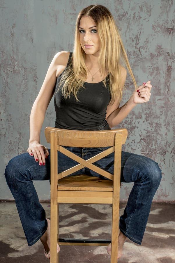 Jong slank blondemeisje in jeans en overhemd die coquettishly stellen stock afbeelding