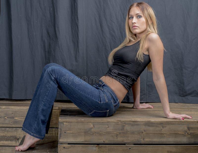 Jong slank blondemeisje in jeans en overhemd die coquettishly stellen royalty-vrije stock afbeeldingen