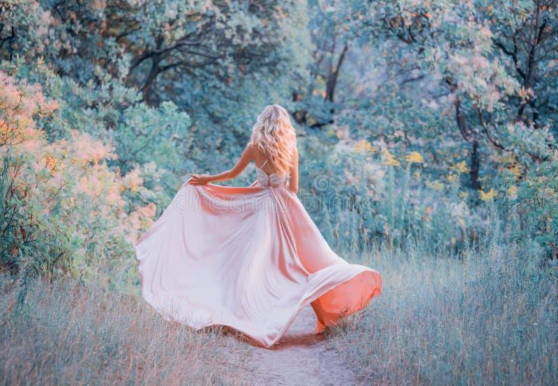 Jong slank goed gevormd meisje met lang blond krullend haar die een elegante roze kleding van de satijn klappende zijde met een k royalty-vrije stock foto