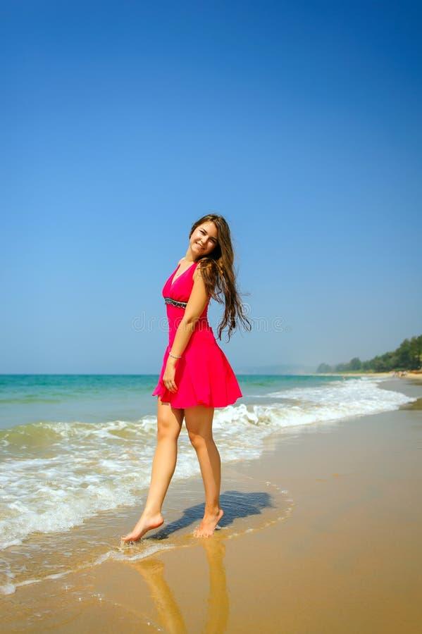 Jong slank langharig brunette in rode kleding die zich blootvoets op tropisch strand met geel zand tegen het overzees en de blauw royalty-vrije stock foto's