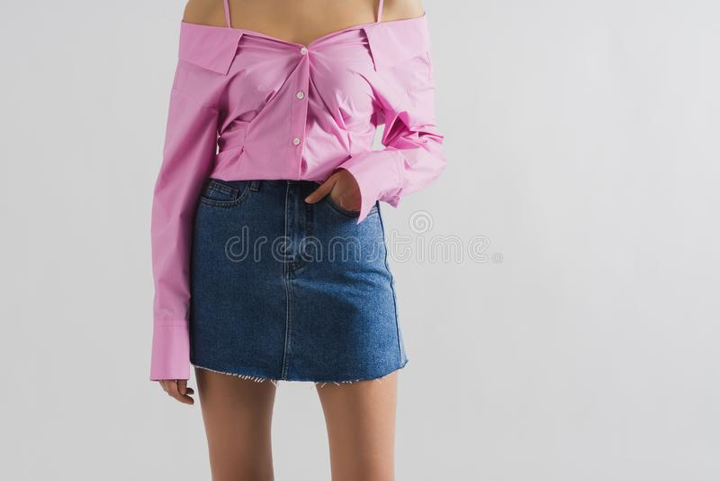Jong slank meisje in korte blauwe denimrok en roze overhemd Witte achtergrondexemplaarruimte royalty-vrije stock fotografie