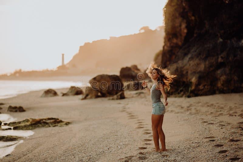 Jong slank mooi vrouwenmeisje op zonsondergangstrand, indie stijl De achtergrond van de rots royalty-vrije stock afbeelding