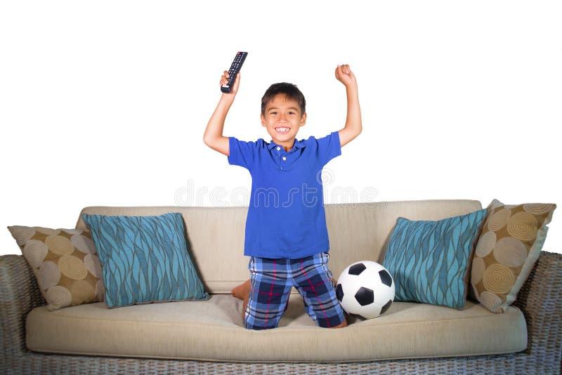 Jong Spaans jongen gelukkig en opgewekt het letten op voetbalspel bij televisie springen opgewekt bij huis het leven laag het vie stock afbeelding