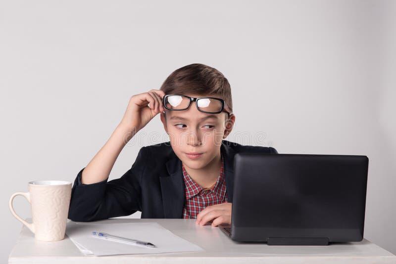Jong speels bedrijfsjong geitje die laptop bekijken stock afbeelding