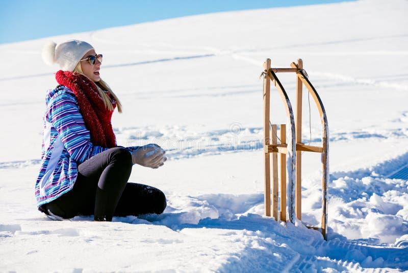Jong speels paar die pret het sledging onderaan sneeuw behandelde heuvel hebben stock afbeeldingen