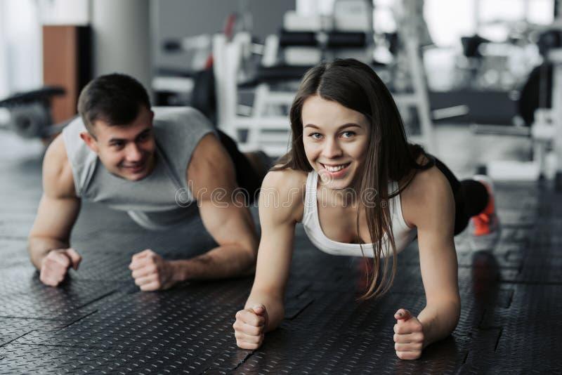 Jong spierpaar die doend harde training bij de gymnastiek doen Het doen van plank in de gymnastiek royalty-vrije stock afbeeldingen