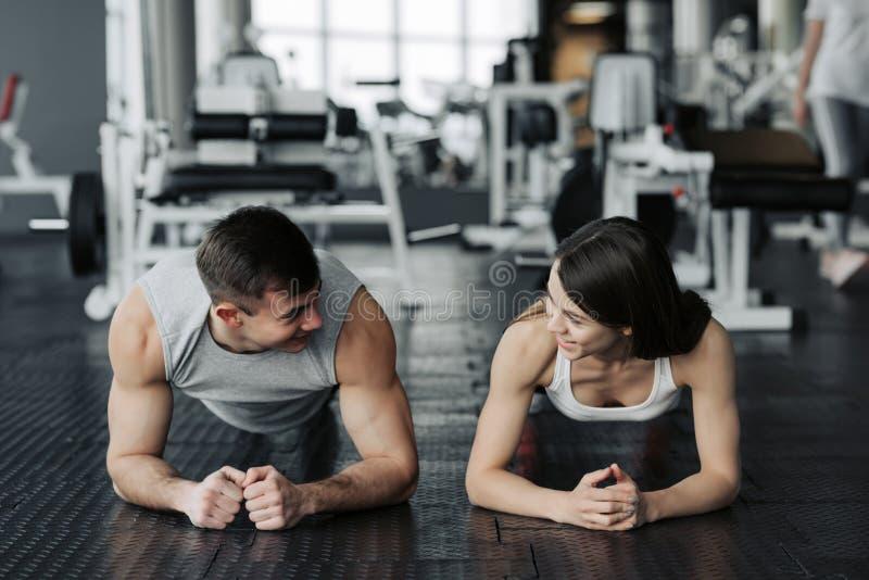 Jong spierpaar die doend harde training bij de gymnastiek doen Het doen van plank in de gymnastiek stock afbeelding