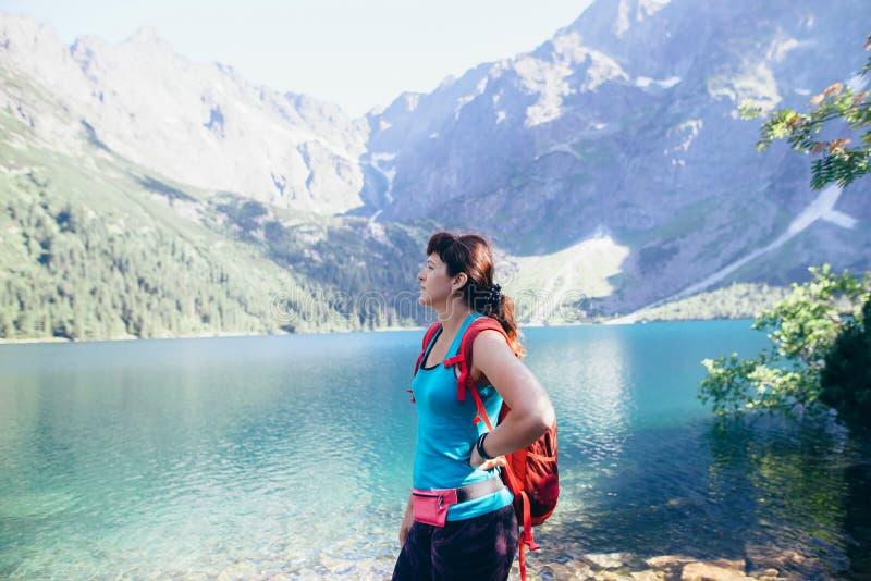 Jong sportenmeisje die in een schilderachtige plaats in het midden van de bergen dichtbij het meer lopen royalty-vrije stock fotografie