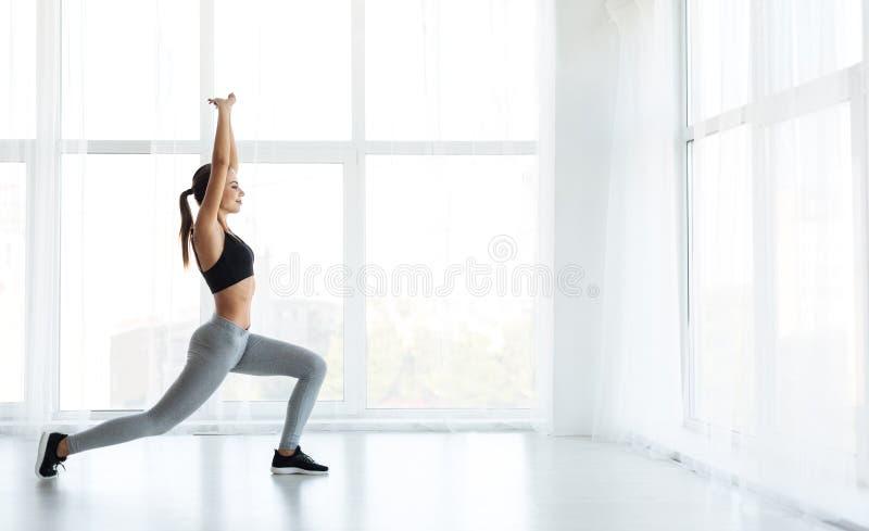 Jong sportief meisje die lichaamsbewegingen doen bij studio royalty-vrije stock foto's