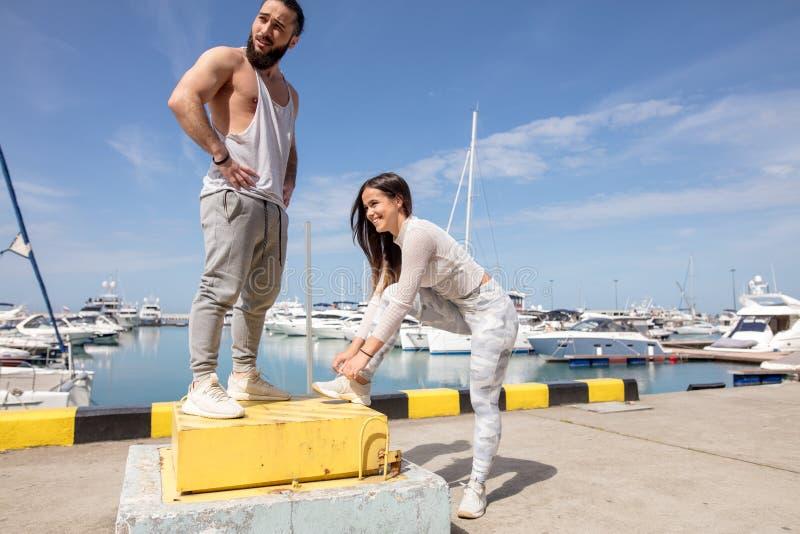 Jong sportief paar die een onderbreking tussen opleiding hebben, die bij pijler voorbereidingen treffen te lopen royalty-vrije stock foto's