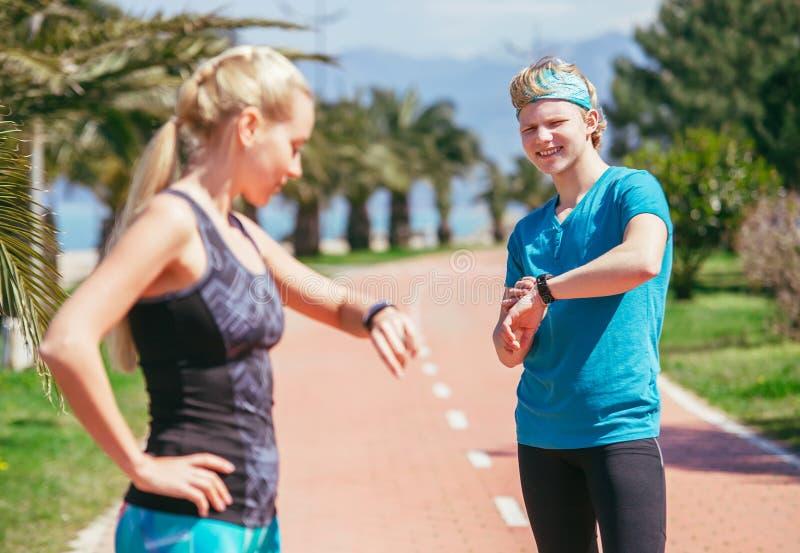 Jong sportief paar die hun tijdopnemer beginnen vóór jogging stock foto's